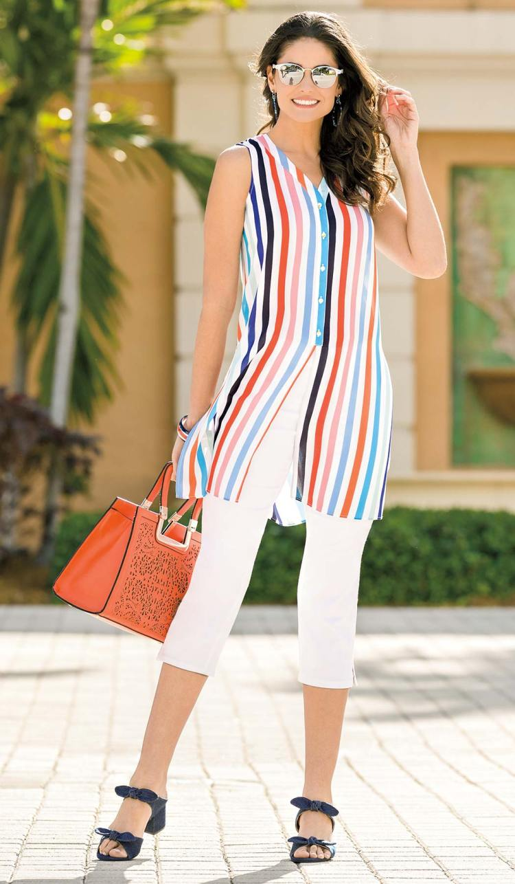 Model wearing a striped flyaway tunic posing with sunglasses and a hand bag