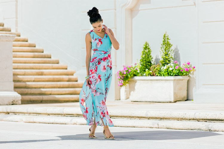 Model wearing a turquoise floral maxi dress blowing in the wind