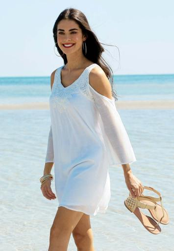 A model walking on the beach with shoes in hand, water in background, wearing a white cold shoulder dress with crochet embroidery.