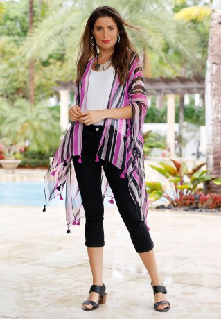 Model standing in front of shrubbery in black crops, black flats, a white tee and purple striped tassel kimono.