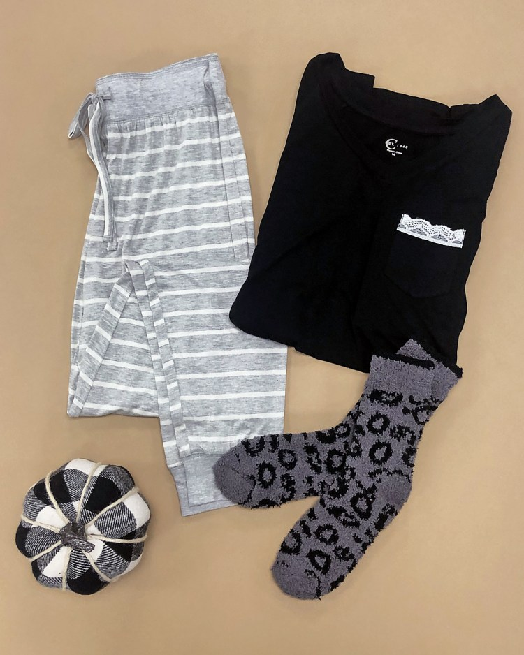black sleep tee with white lace pocket, heather gray and white striped jogger sleep pants, and fuzzy gray leopard cozy socks