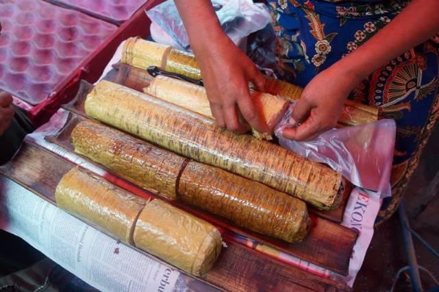 Lemang dijual dengan dibungkus daun pisang, ditaruh diatas bambu.