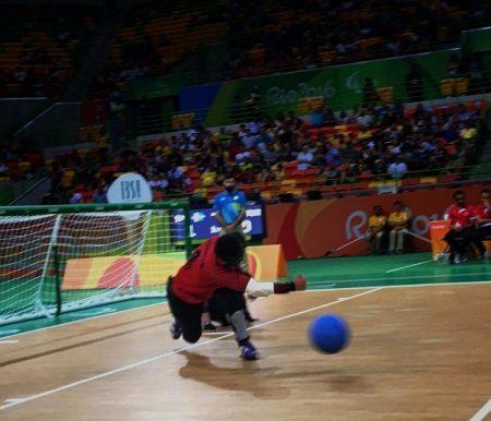 No primeiro plano,bola de goolbol azul flutuando em alta velocidade, à frente do jogador. Cor da pele morena, cabelos pretos, vestindo uniforme na cor vermelha, com calças pretas , em posição de ataque agachado com a perna direita levantada e o braço direito à frente fazendo o movimento de lançamento da bola. Ao fundo arquibancada com os torcedores e ao lado direito da imagem a trave.