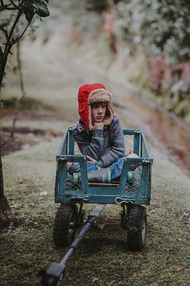 Petite fille pensive dans une remorque de vélo