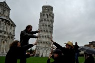 Leaning tower of Pisa, with tourists, in the rain