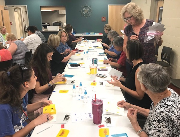 Instructor helping students during craft class