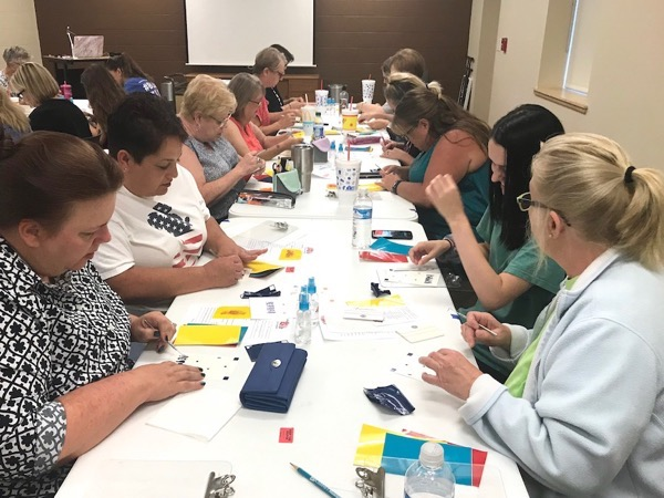 Group of students making layered adhesive vinyl decals during craft class