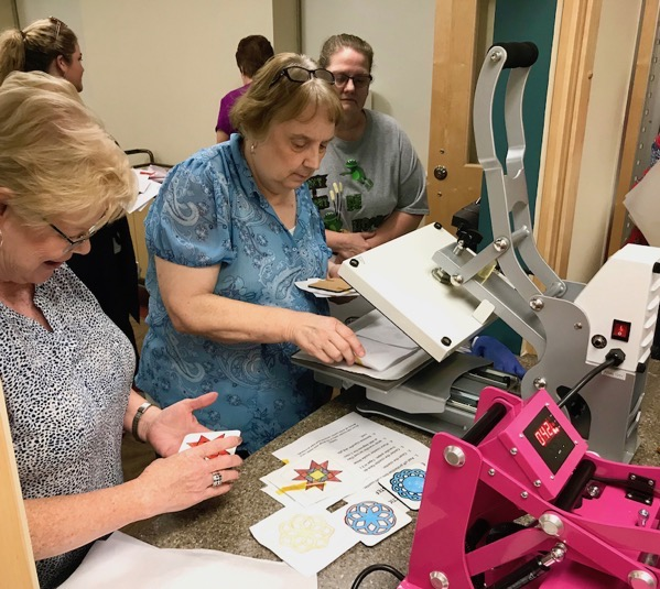 Group of women using Craft Pro heat press for sublimation coasters