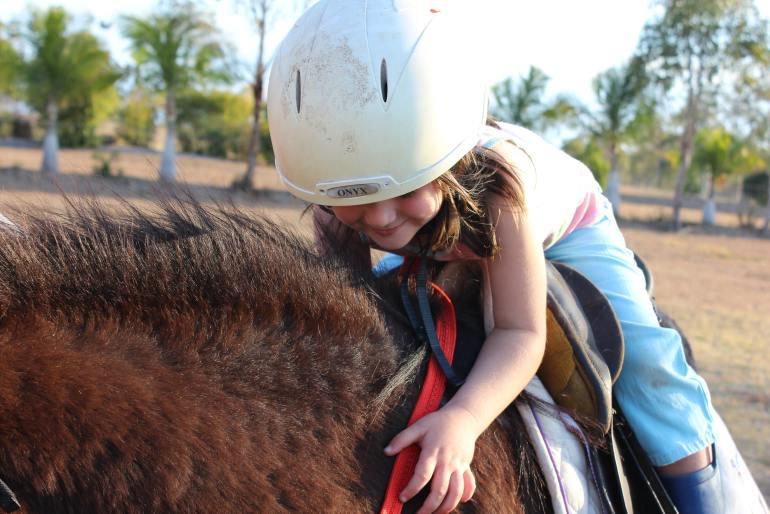 criança montada a cavalo