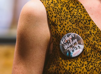 """woman wearing a badge: """"40 years of unlocking the law"""""""