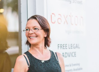 """A caxton client stands in front of the """"Free Legal Advice"""" sign at Caxton Legal Centre"""
