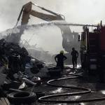 Fire crews work on deep-seated fires amid scrap metal