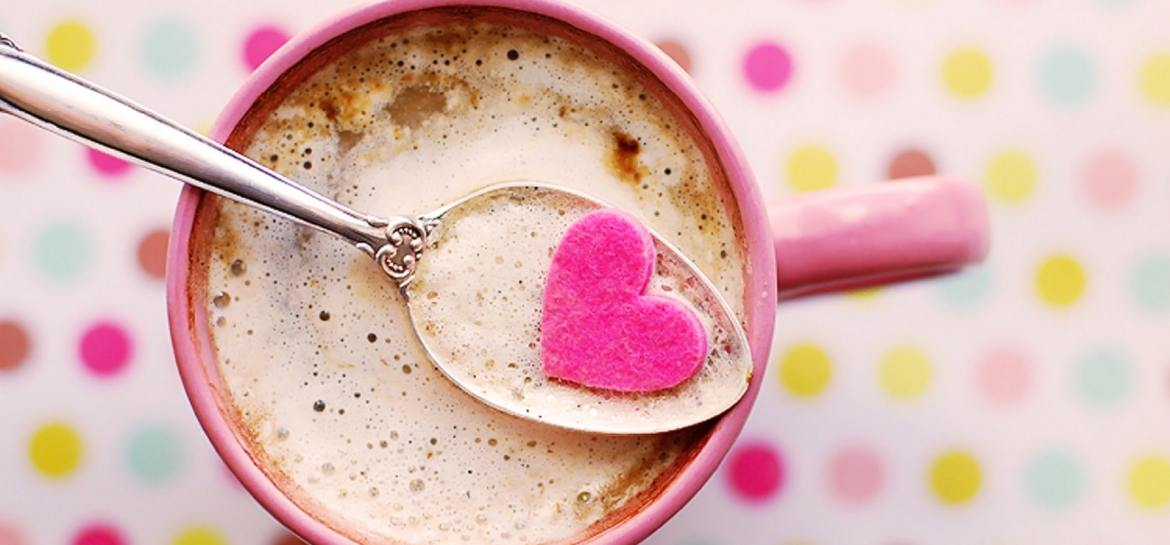 Cup of coffee on pink spotty background
