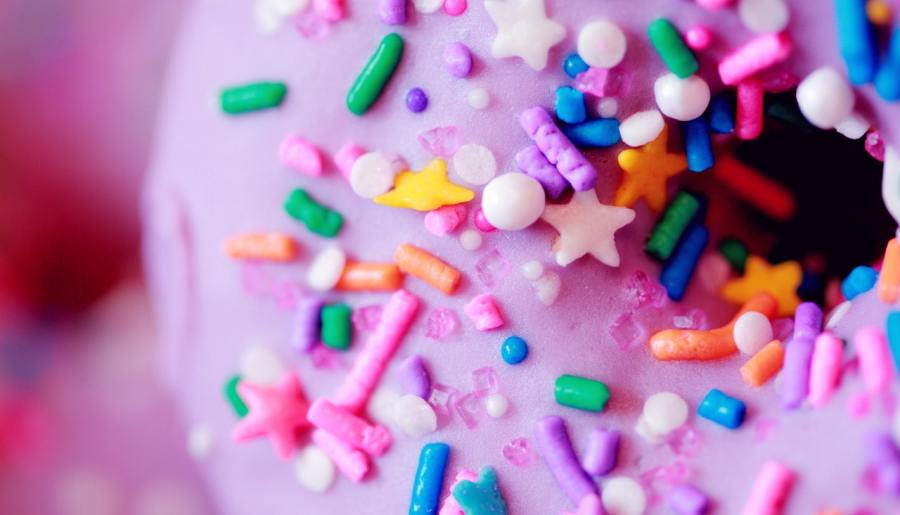 Close up of pink doughnut with sprinkles