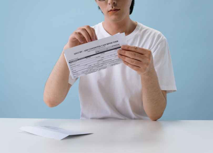 man in white t shirt holding hiv aids paper form