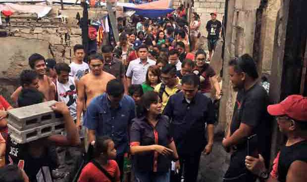 Robredo back from USA, visits NIA road fire victims