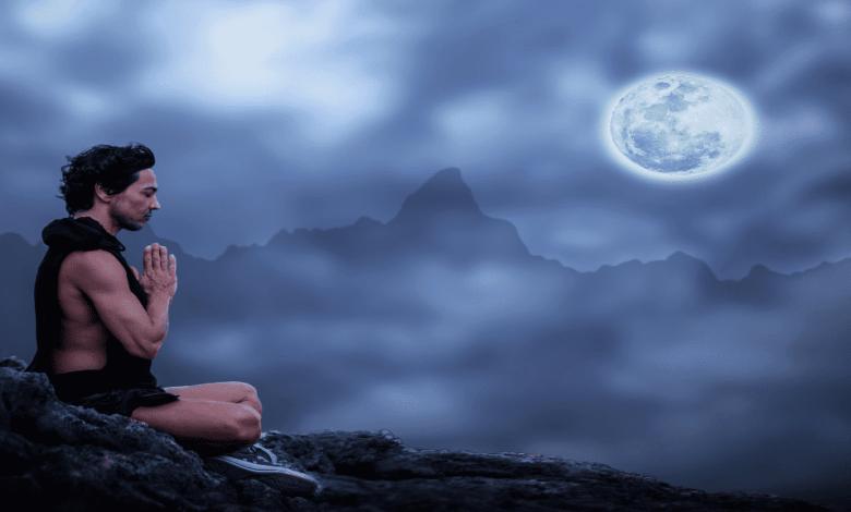 un homme qui médite et éclairé par la pleine lune