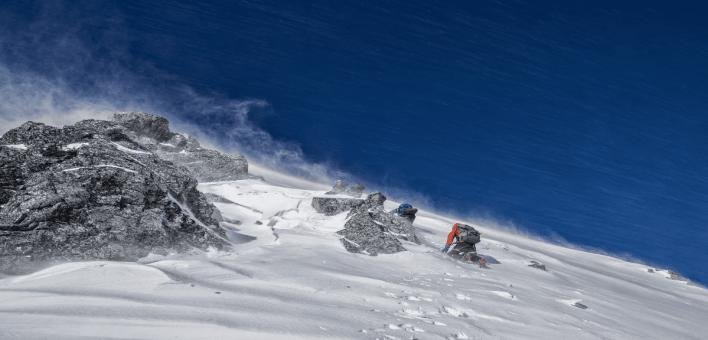 un groupe d'alpiniste escaladant une montagne recouverte de neige
