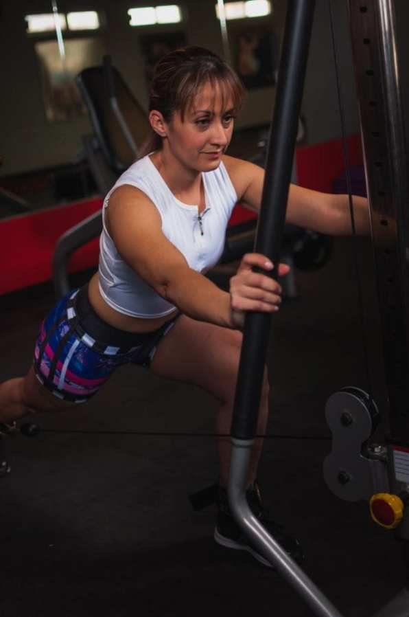 photo of woman working out using gym equipment inside gym