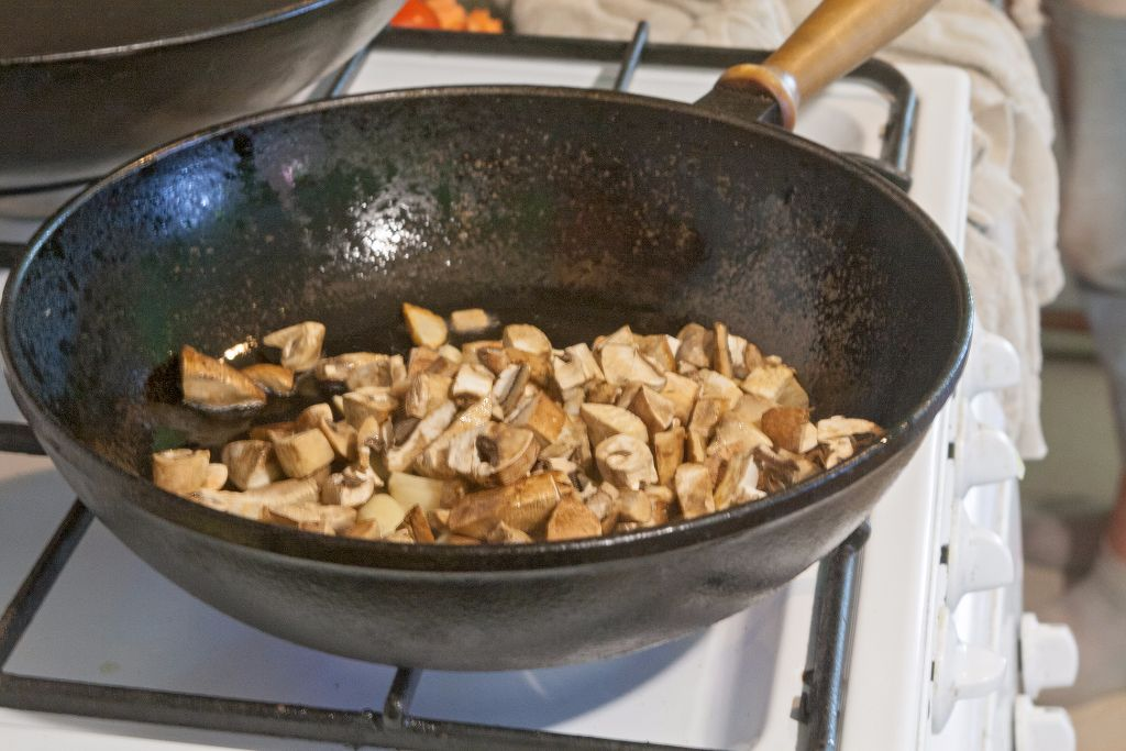 Adding the sliced mushrooms to the garlic