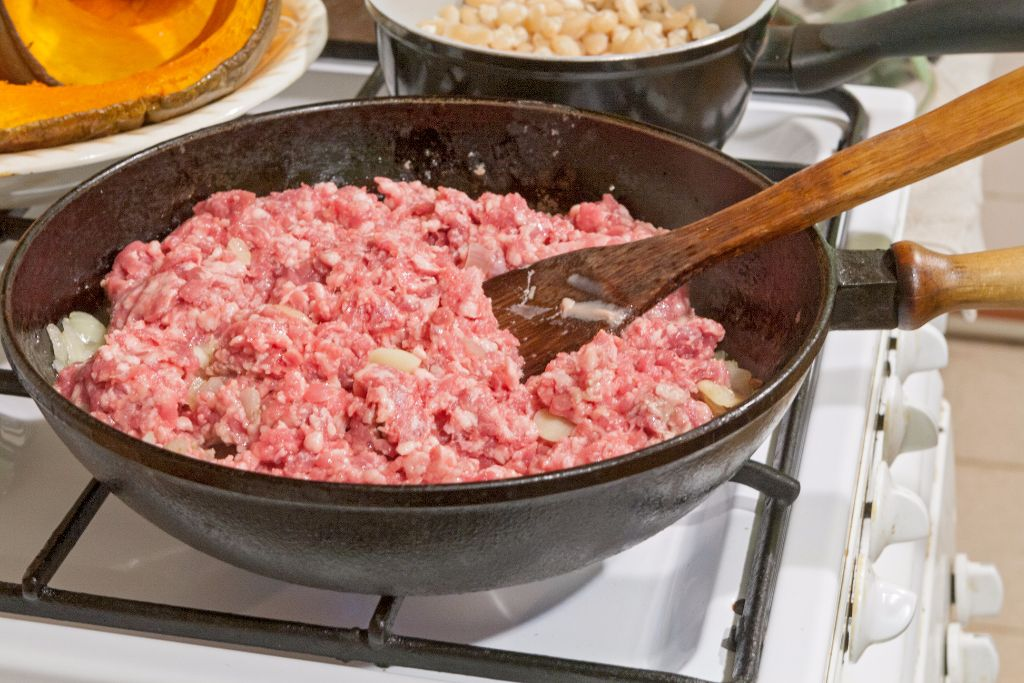 Adding the minced pork to the skillet