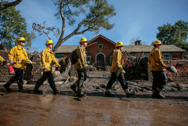 Rescue workers enter properties to look for missing persons after a mudslide in Montecito, California,