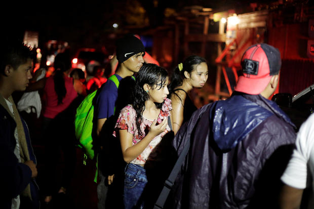 Hondurans, part of a new caravan of migrants travelling towards the United States, are seen as they wait to catch a ride in Cofradia