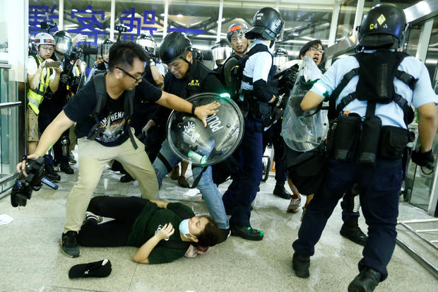Police clash with anti-government protesters at the airport in Hong Kong,