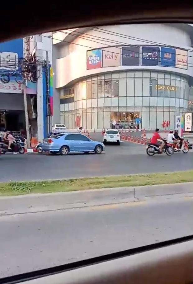 A person runs away from a shopping mall during a shooting rampage in Nakhon Ratchasima