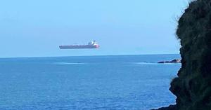 The photos appear to show a giant ship hovering over the water off the coast of England