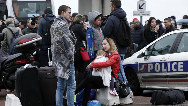 Travelers wait outside the Orly airport, south of Paris, March 18, 2017.