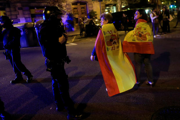 Pro unity demonstrators wear Spanish flags as they walk past Catalan Regional Police officers during a protest after the Catalan regional parliament declared independence from Spain in Barcelona