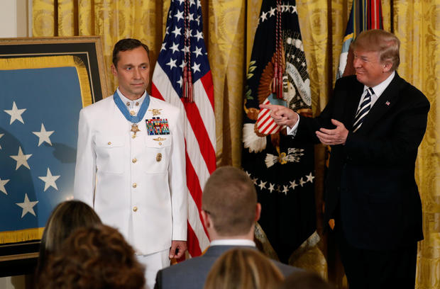 """U.S. President Donald Trump gestures after awarding the Medal of Honor to Retired Navy Master Chief Special Warfare Operator Britt Slabinski for """"conspicuous gallantry"""" in the East Room of the White House in Washington"""