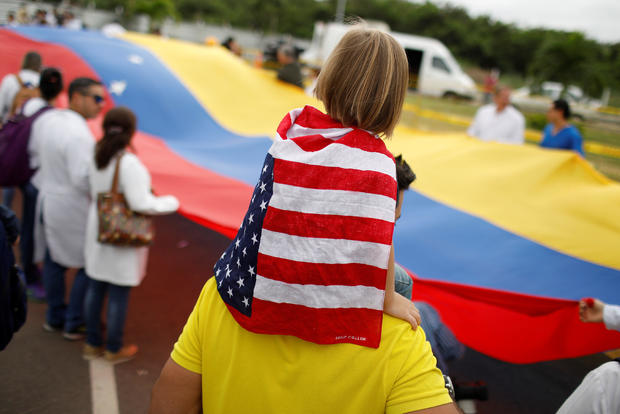 A child wearing a U.S. flag attends a gathering of Venezuelan doctors at the entrance of a warehouse where humanitarian aid for Venezuela is being stored near the Tienditas cross-border bridge between Colombia and Venezuela in Cucuta