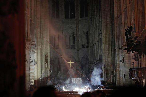 La fumée monte autour de l'autel devant la croix à l'intérieur de la cathédrale Notre-Dame tandis qu'un incendie continue de brûler à Paris