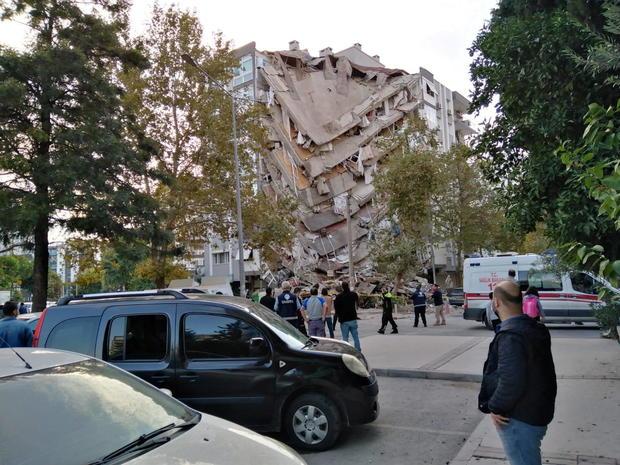 Locals look at a damaged building in Izmir
