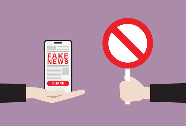 Businessman show prohibition sign to fake news