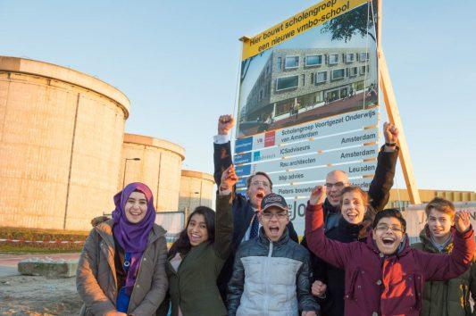 Wethouder Onderwijs, Simone Kukenheim, en voorzitter Raad van Bestuur Voortgezet Onderwijs van Amsterdam, Edo de Jaeger, onthullen samen met leerlingen het bouwbord met het ontwerp van de nieuwe school (Foto: Dennis Goedbloed).