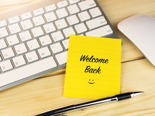 keyboard with Welcome Back written on a sticky note