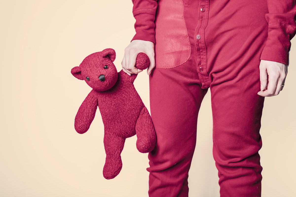 Child in red pajamas holding red teddy bear