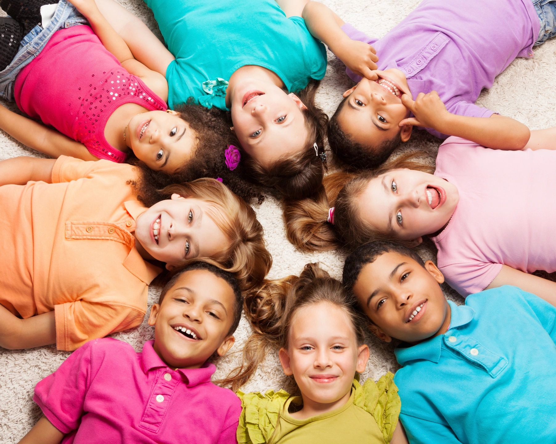 Group of children wearing colorful shorts laying on the ground in a cirle with their heads touching in the middle of the circle