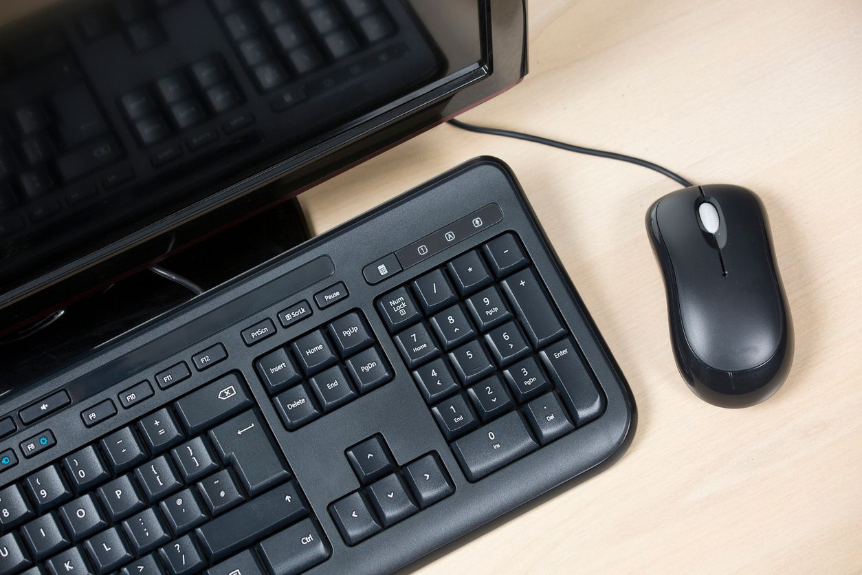 Black computer, keyboard and mouse on a desk