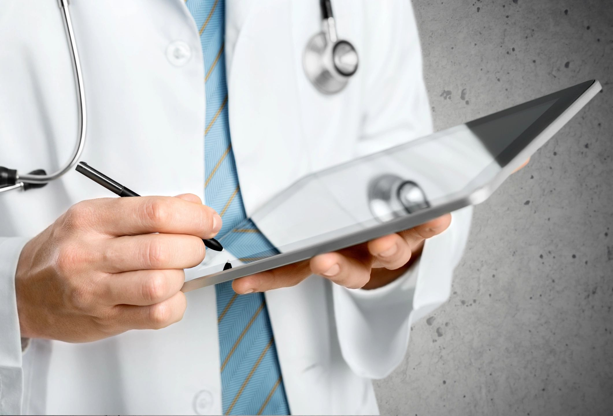 Doctor holds a tablet and writes on it with a stylus