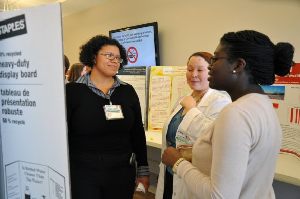 (From left to right) Razel Remen, MD, a second-year resident, Cynthia Mouton, MD, a third-year resident, and Brittney Anderson, a third year medical student, discuss a research poster at the College's Sixth Annual Research Day.
