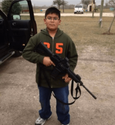 Young boy holding a rifle. Photo by Jacob Benavides.