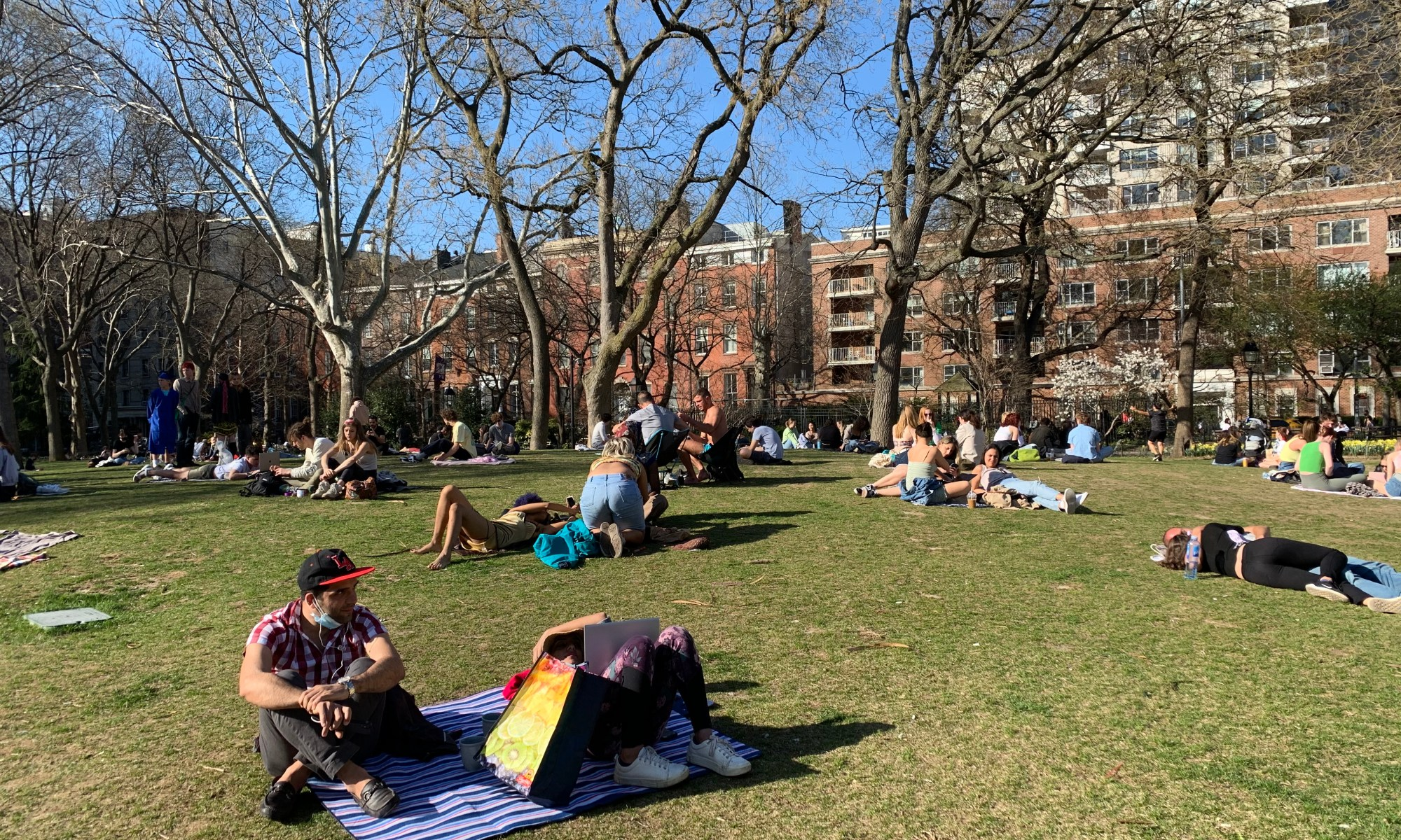 People on the grass in Washington Square Park in early spring