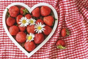 Strawberries and daisies in a heart mold on a checkered blanket