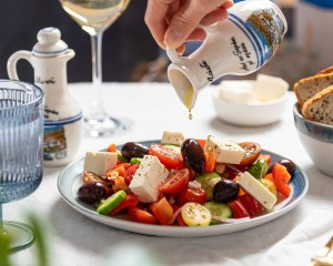Image of olive oil being poured on a Greek salad