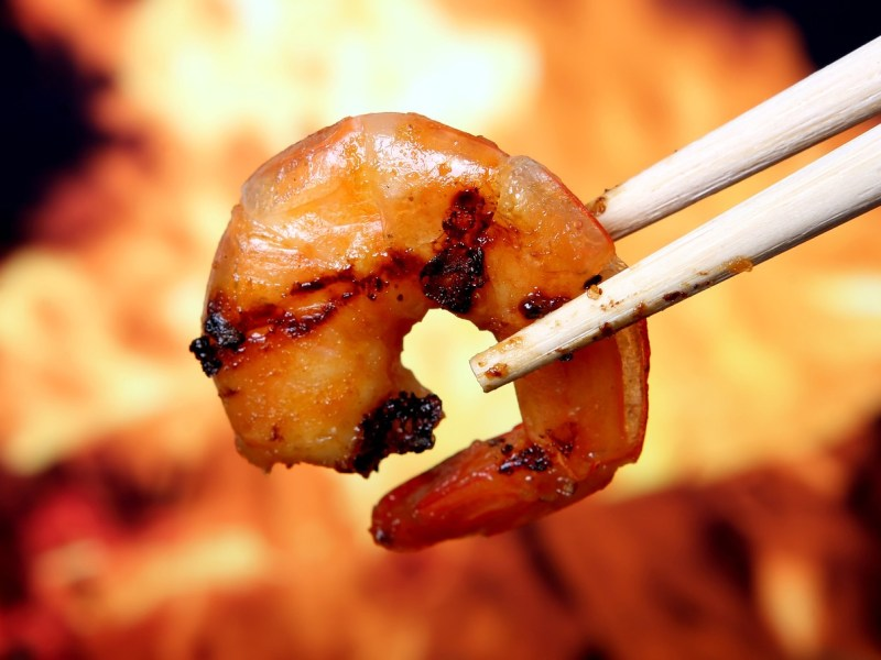 Grilled shrimp with flames in the background