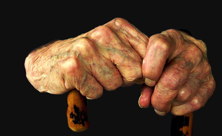 old hands holding a cane